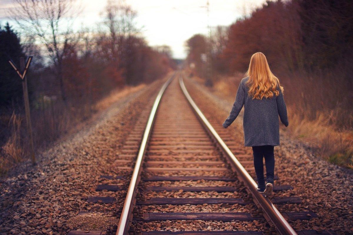 Woman walking Railroad Tracks